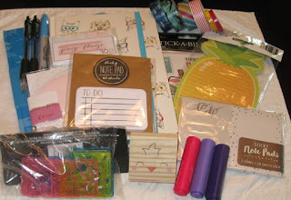 My goodies: some cute journals, stickers, a pineapple notepad, mini highlighters, washi tape, cute stencils, post it notes, a cat journal, pens, and a cat stamp.