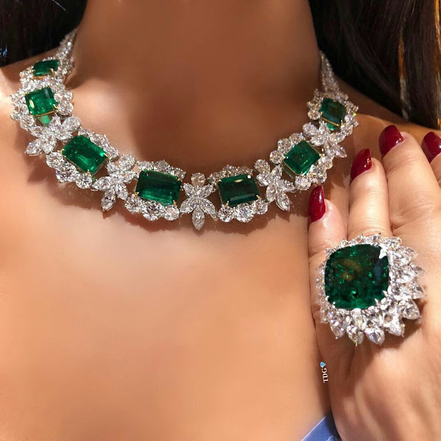 A close up photo of an emerald and diamond ring and necklace while being worn.