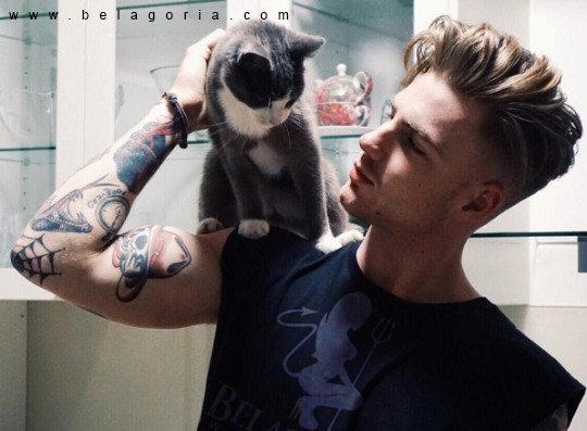 Vemos a un hombre joven con un gato, el chico lleva tatuajes old school en los brazosç