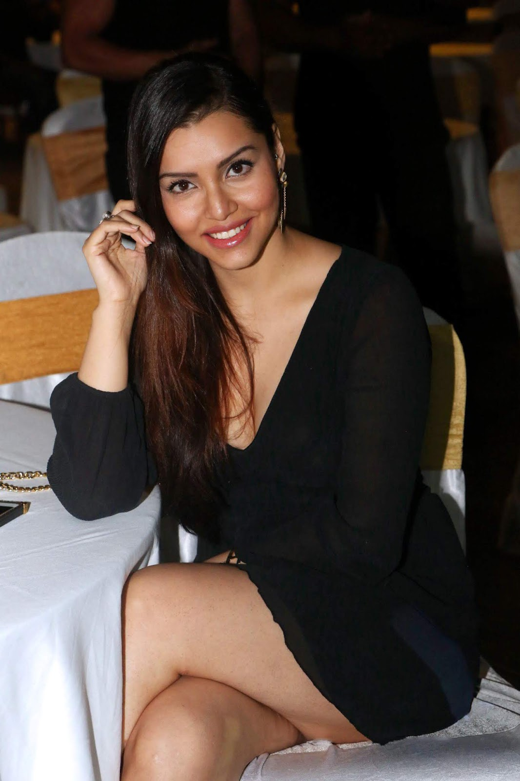 Kyra Dutt in black mini frock skirt sitting crossed legs on a chair