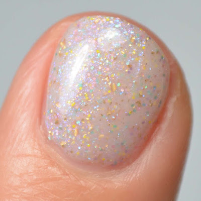 off white nail polish with sparkles and color shifting flakies swatch close up