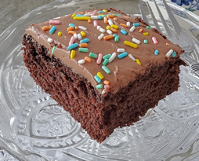 chocolate slice of cake with frosting on top with sprinkles on a crystal plate