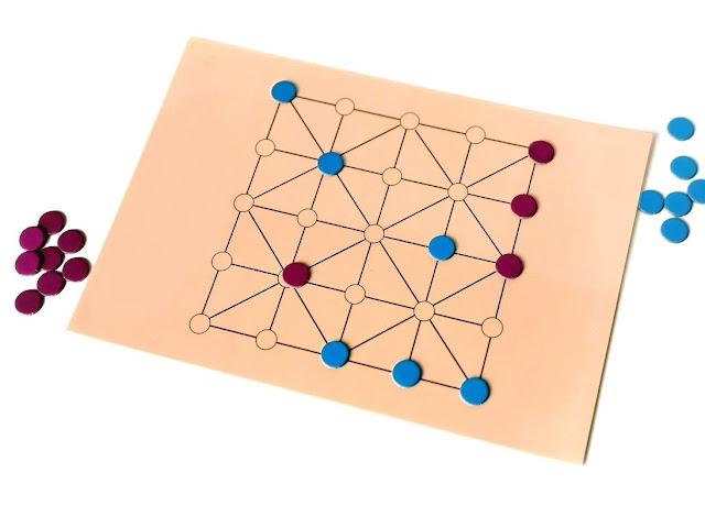 na zdjęciu plansza w trakcie gry, część z pionków jest już zbitych i leża koło planszy