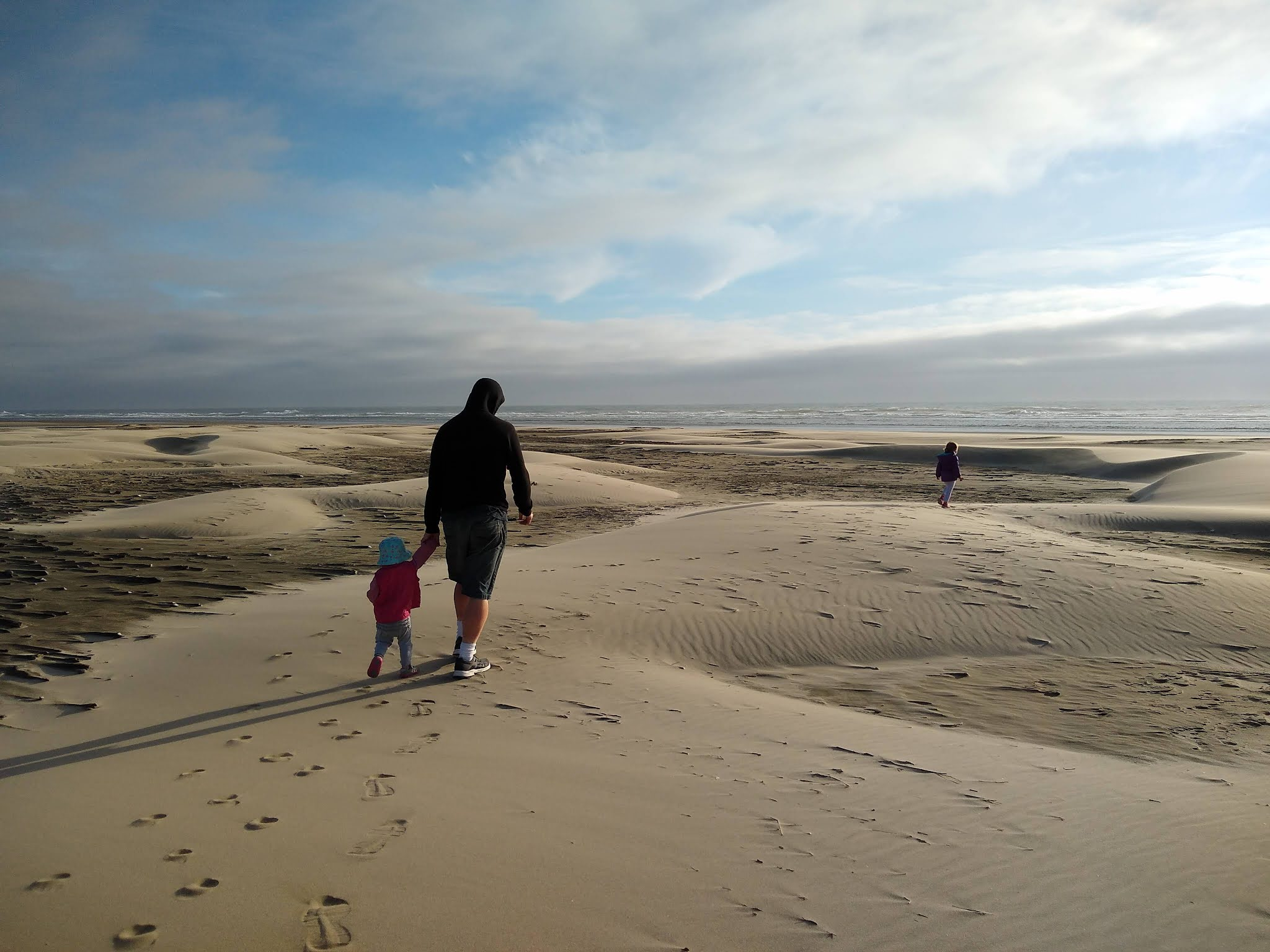 A toddler holding her father's hand on a sandy beach.