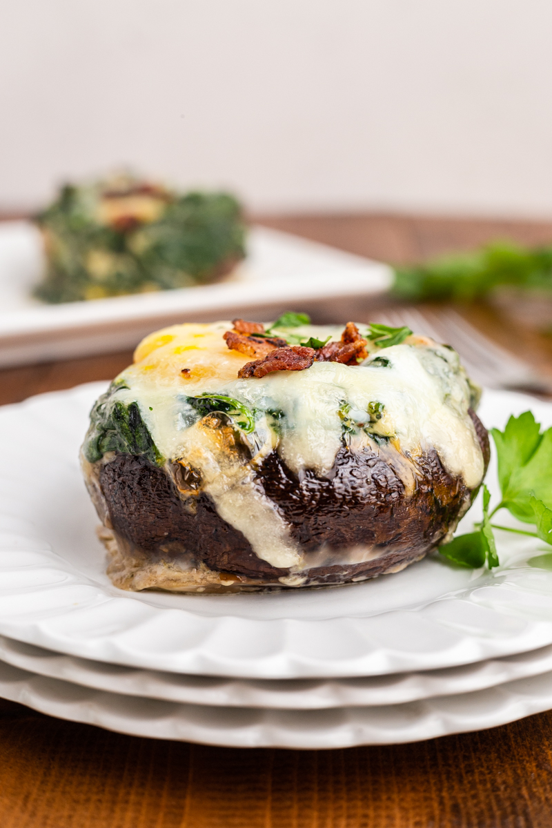 Photo of a Keto Spinach and Egg Stuffed Mushroom on a white plate with a platter of them in the background.
