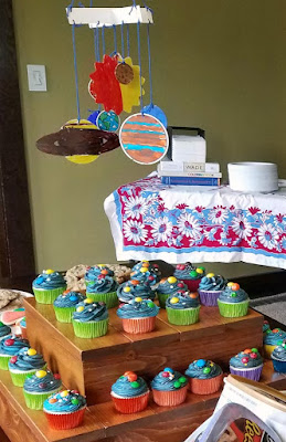 solar system cupcakes on cupcake stand boxes with colored planets mobile hanging above it