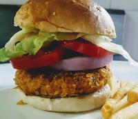Arranged burger patty and vegetables covered with half of the sesame seeds bun for veg burger recipe