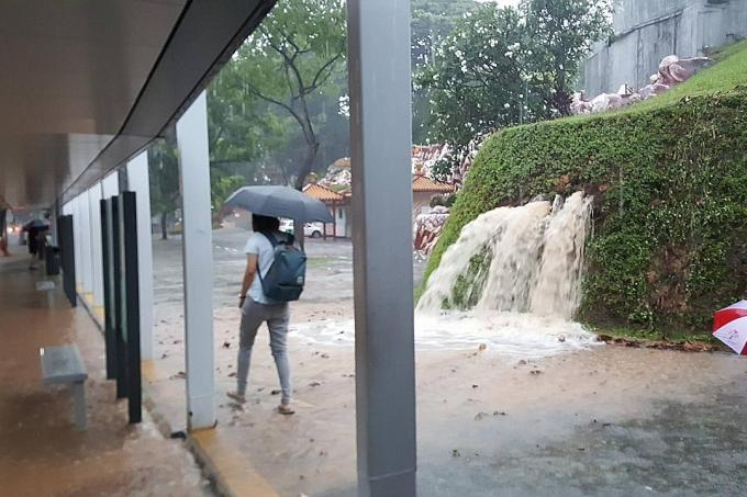 Water gushing from drains near the bus stop outside Haw Par Villa MRT station during a downpour yesterday.
