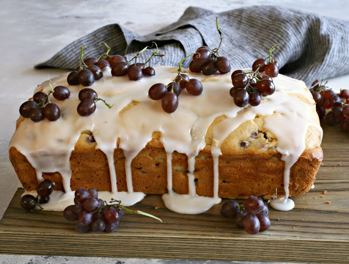 Recipe for a loaf cake baked with champagne grapes and topped with a lemon glaze.