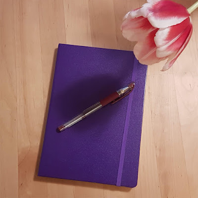 A purple notebook, burgundy pen, and a red-and-white tulip flower