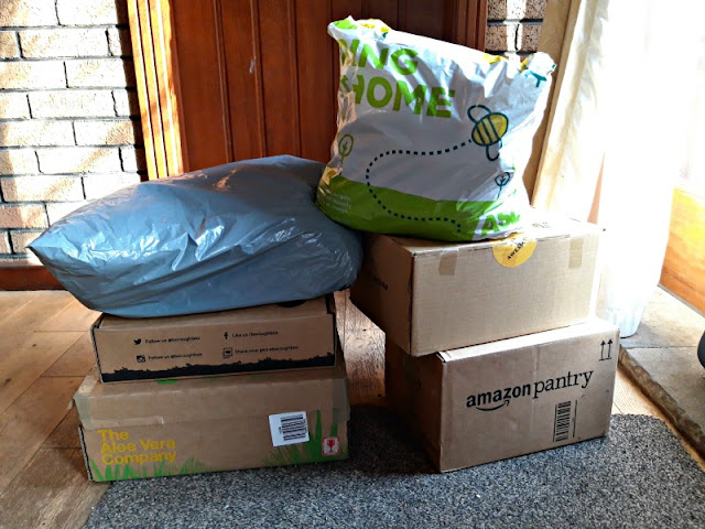 A photo showing two piles of parcels sitting on a brown speckled front door mat.  Behind is a closed wooden door and a decorative brick internal wall.  The sun is streaming through a window on the right.  There are four cardboard boxes, one grey plastic mail bag and a reuseable shopping bag in the pile.  The boxes of socks are ready to be posted out.