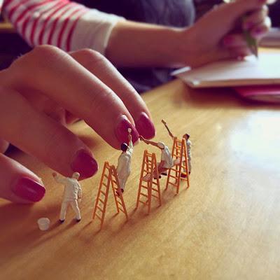 Pequeños hombrecitos dejando uñas pintadas de una mujer