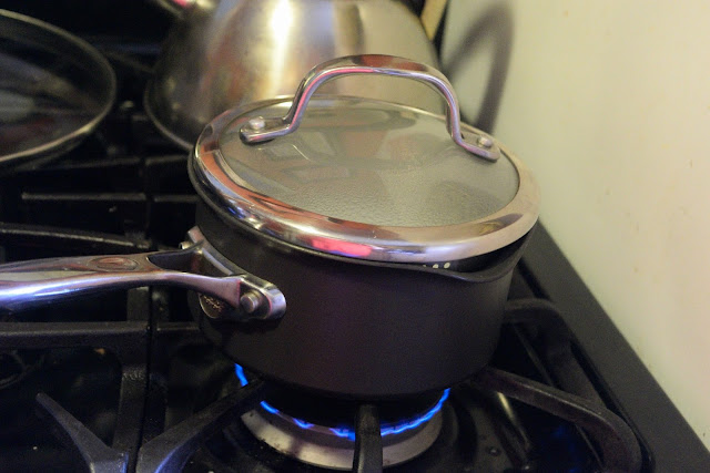 The sauce pot over medium/high heat with the lid on it.