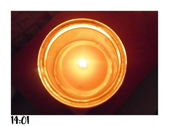 paląca się świeczka na pomarańczowym notesie.