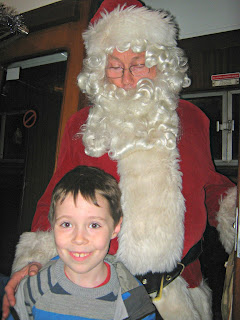 Boy with very tall Father Christmas standing behind