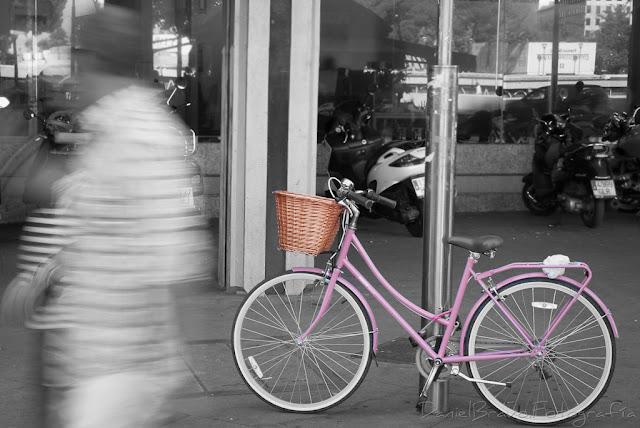 Fotografía de una bicicleta de color rosa con el fondo en blanco y negro