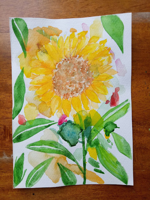 Sunflower watercolor painting filled with lots of green leaves and yellow petals