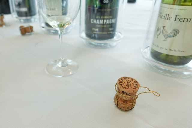 A champagne cork, a glass and wine bottles in the background