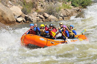 A raft filled with six guests paddling down a river in rapids on a sunny day.