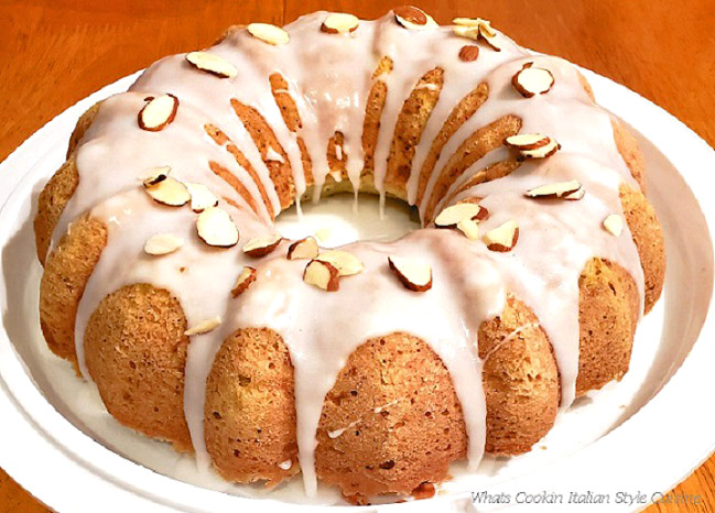 this is my zucchini almond poppy seed bundt cake on a white plastic carry dish with white frosting and slivered almonds on top
