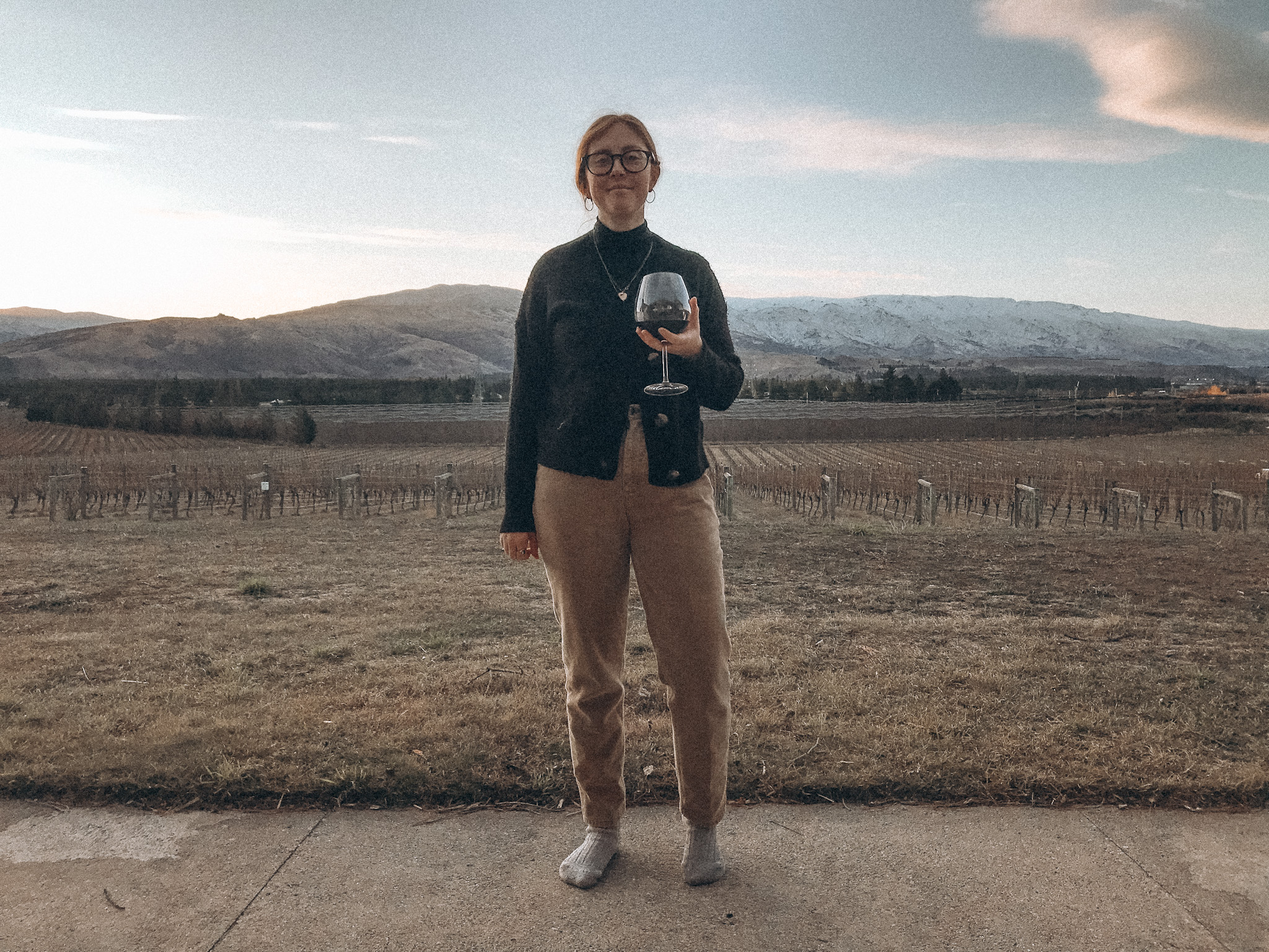 Amy is in a vineyard in new zealand wearing a black top and sand coloured trousers holding a large glass of red wine