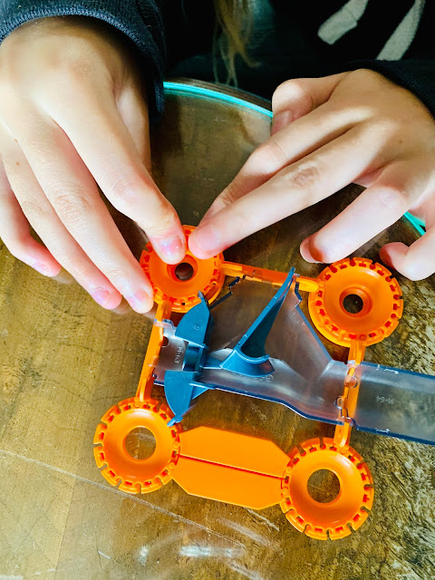 hands building Geomag magnetic race track