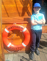 Boy standing next to the lifebelt on The Matthew