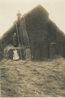 Shows nearly completed Hay Rick. Man up ladder which is held by lady in long dress. Another women is at bottom of ladder with girl who is holding 2 jugs.