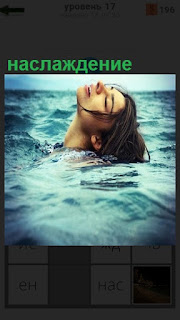 На воде лежит девушка, только одна голова видна, испытывает наслаждение