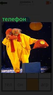 Клоун в желтом с красным игрушечным телефоном на сцене