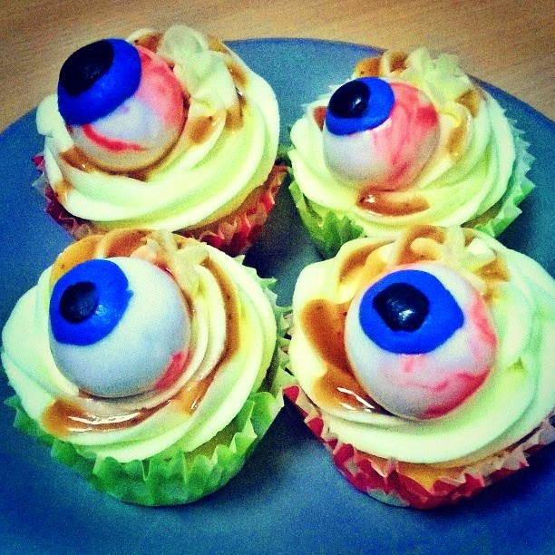 Vanilla frosted cupcakes in red and green cases with eye ball decorations