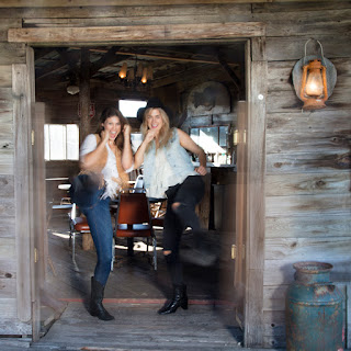 Two girls dressed in western clothing kick down a saloon style door at the Austin, Texas Ghost Town, JLorraine in Manor