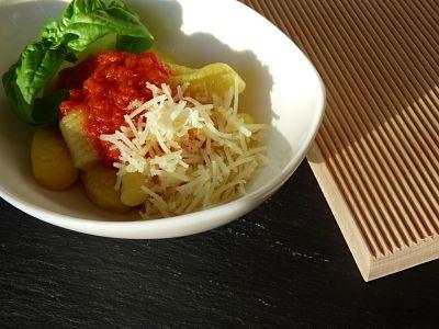 Ñoquis con salsa pomarola casera, queso y albahaca. A su lado, la ñoquera.