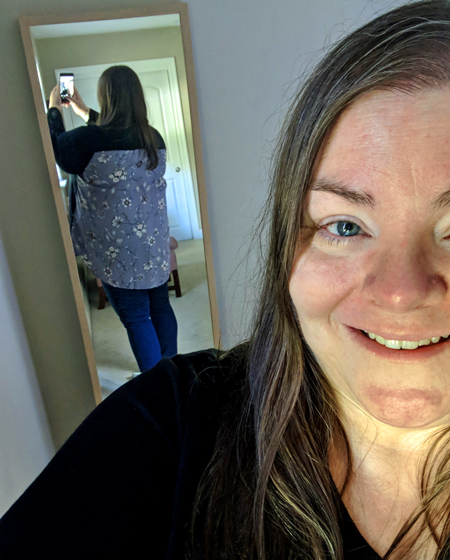 image of part of my face, smiling, with the camera hoisted above my shoulder to capture my back side in the mirror