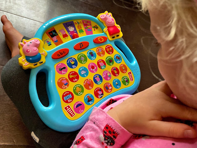A view looking down behind a preschoolers head as she looks at the Peppa's laugh and learn alphaphonics toy from Trends Uk