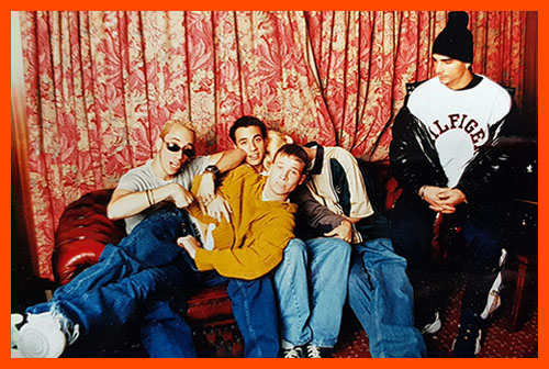 Backstreet Boys messing about on a sofa in front of tasteless curtains
