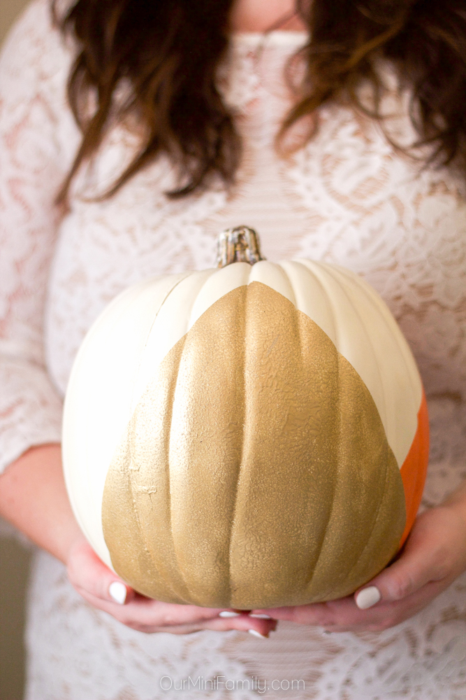 Woman in white lace holding a painted pumpkin