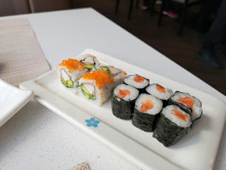 A white rectangular plate filled with black square pieces of sushi with red square pieces and white rice on a white rectangular table on a bright background