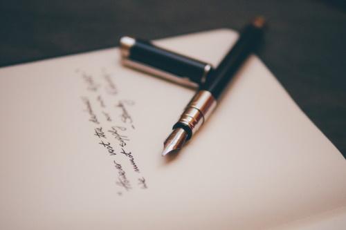 #PraCegoVer: Mão escrevendo.