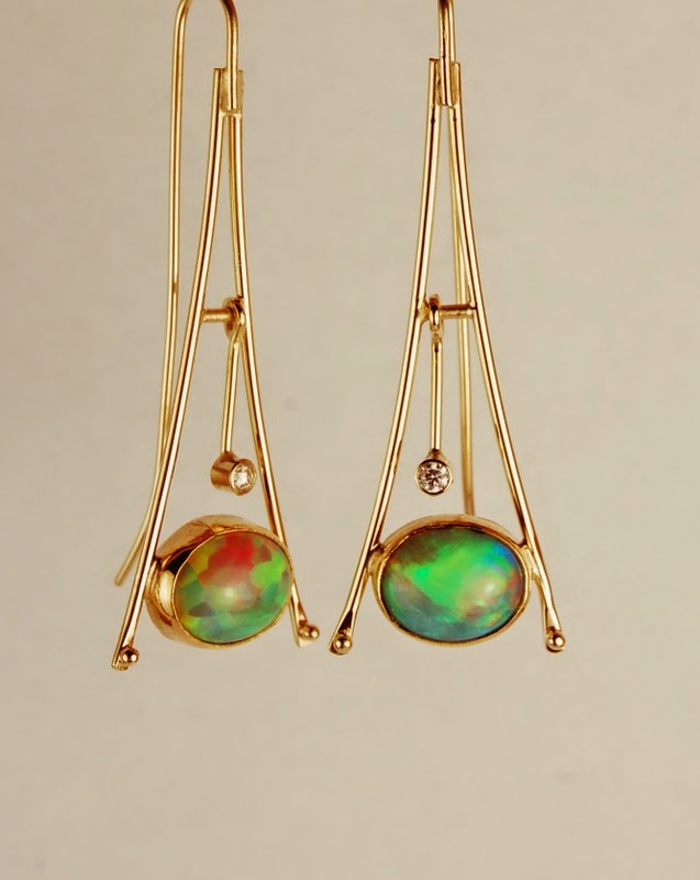Triangular shaped earrings with oval multicolored opals and a swinging diamond