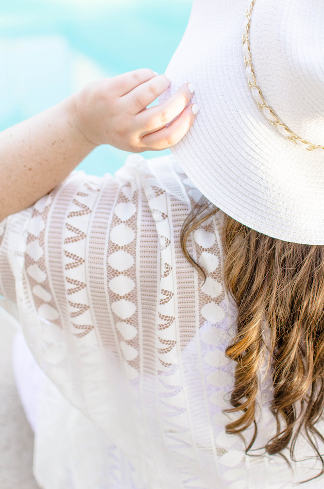 Woman wearing all white holding a sunhat next to the pool