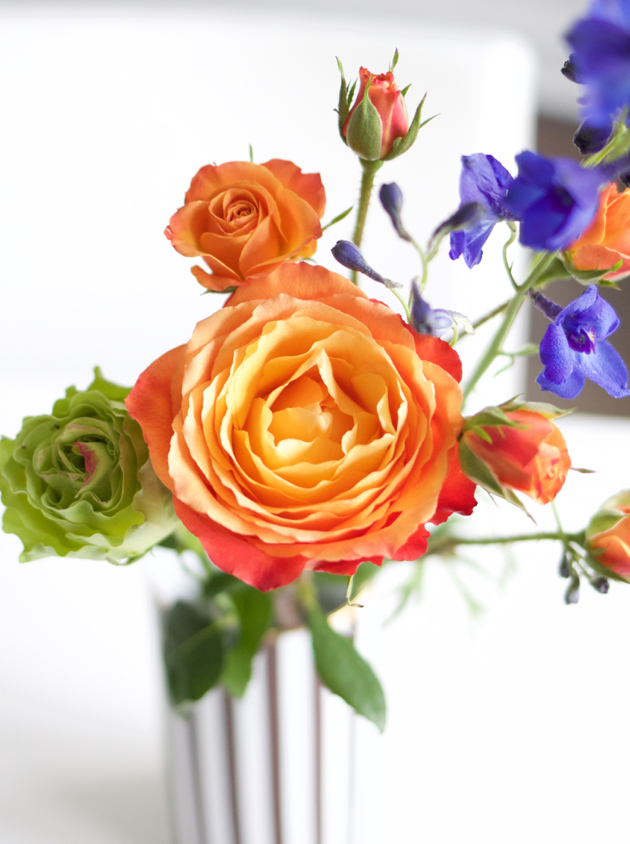 Vase with orange, purple and green roses
