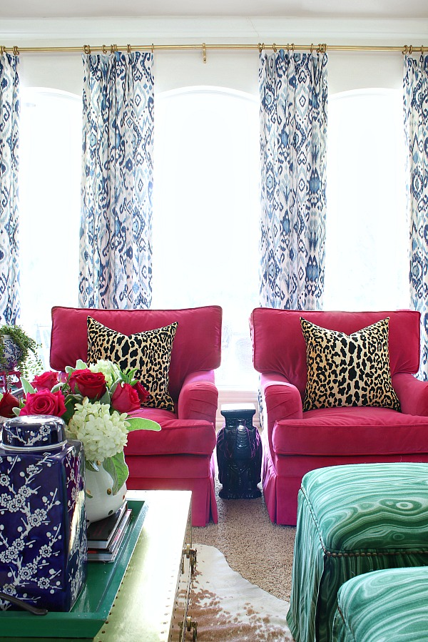 pink velvet chairs, leopard pillows, blue ikat curtains, pair of club chairs