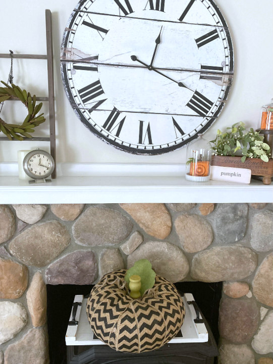mantel and large clock with chevron pumpkin on the wood burning stove.