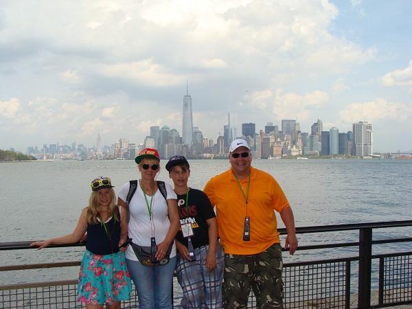Wir stehen auf  Liberty Island mit einem Blick auf die Skyline von Manhattan im Hintergrund