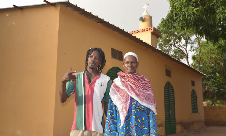 A Rastafarian stands with Lassa's Imam