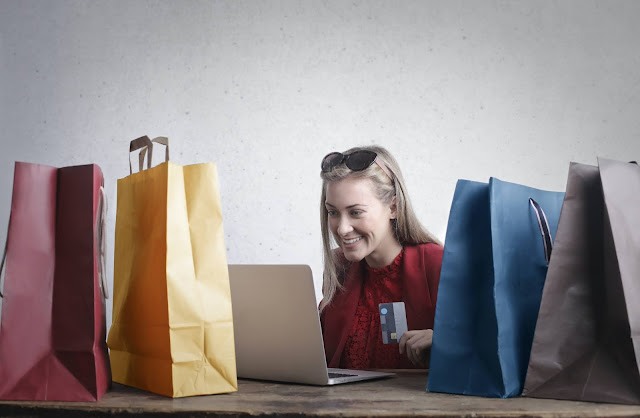 Blonde girl holding a credit card and smiling in front of her laptop.