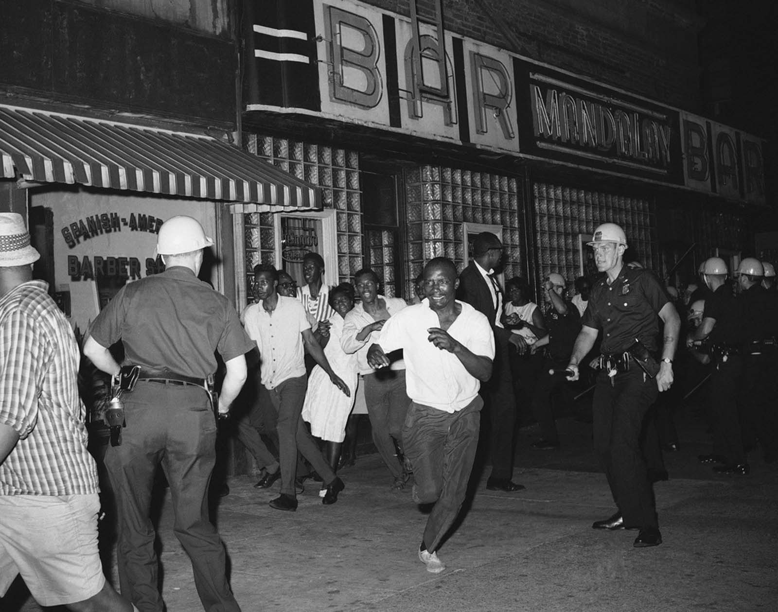 Members of New York's Harlem community run from steel-helmeted police swinging night sticks in effort to break up street gathering on July 19, 1964. The mood of the crowd was ugly following demonstrations during the night from July 18 to 19 and funeral services on July 19 for James Powell.