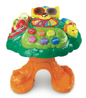 A plastic tree shaped table with activities on top including buttons and a shape sorter