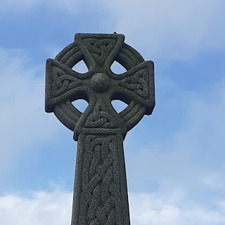Granite celtic cross, carved with knotwork, against a blue sky